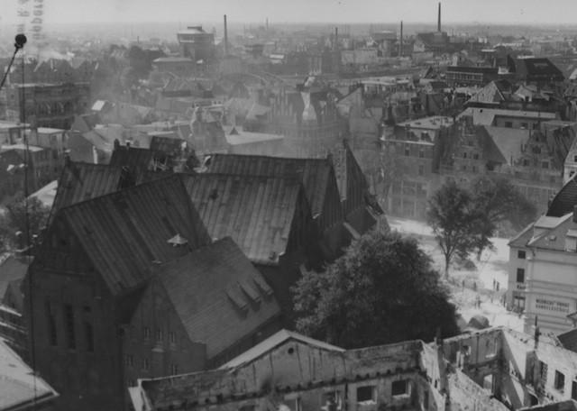 Die St. Ansgarii-Kirche kurz nach dem Einsturz des Turms am 1. September 1944. Aus der Schneise im Dach steigt Trümmerstaub empor. Bildvorlage: Staatsarchiv Bremen