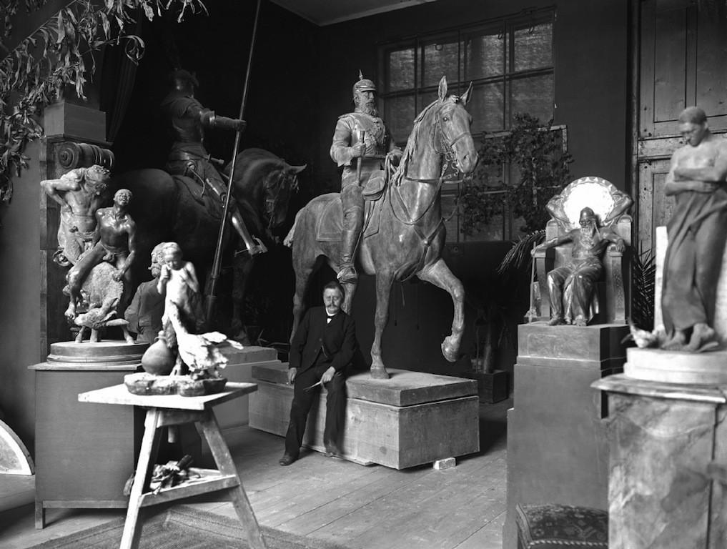 Rudolf Maison in seinem Münchener Atelier. Links im Hintergrund ist eine der beiden Heroldsfiguren zu sehen. Quelle: Wikicommons