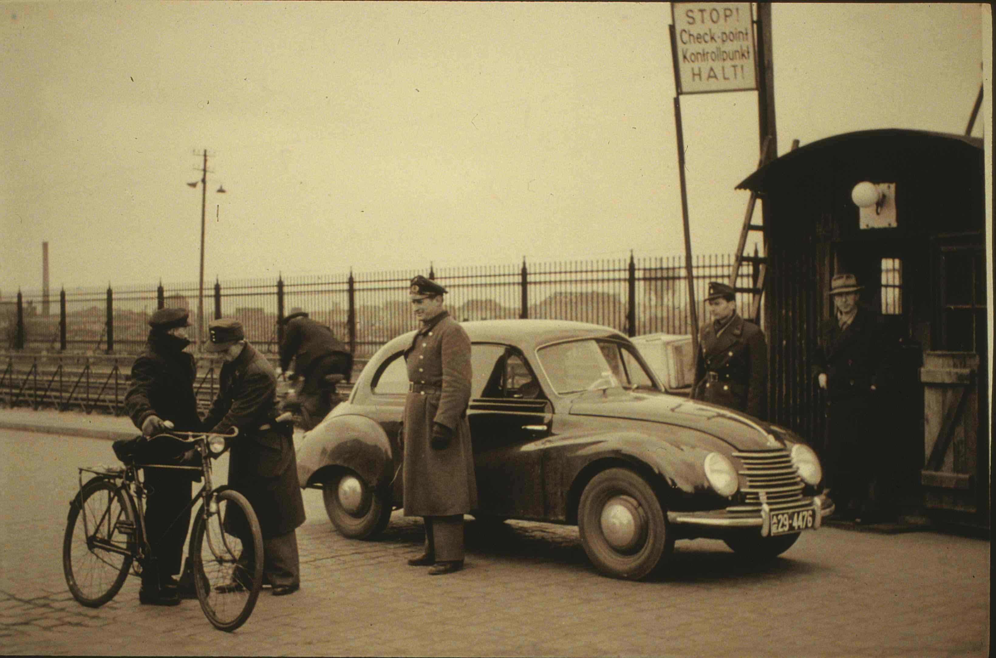 Vertrauen ist gut, Kontrolle ist besser: Personenkontrolle an einem Wachtposten am Bremer Freihafen. Das Foto ist vermutlich in den frühen 1950er Jahren entstanden, darauf weist das bis 1956 ausgegebene amerikanische Kennzeichen mit dem Kürzel AE für Amerikanische Enklave hin. Quelle: Kulturhaus Walle