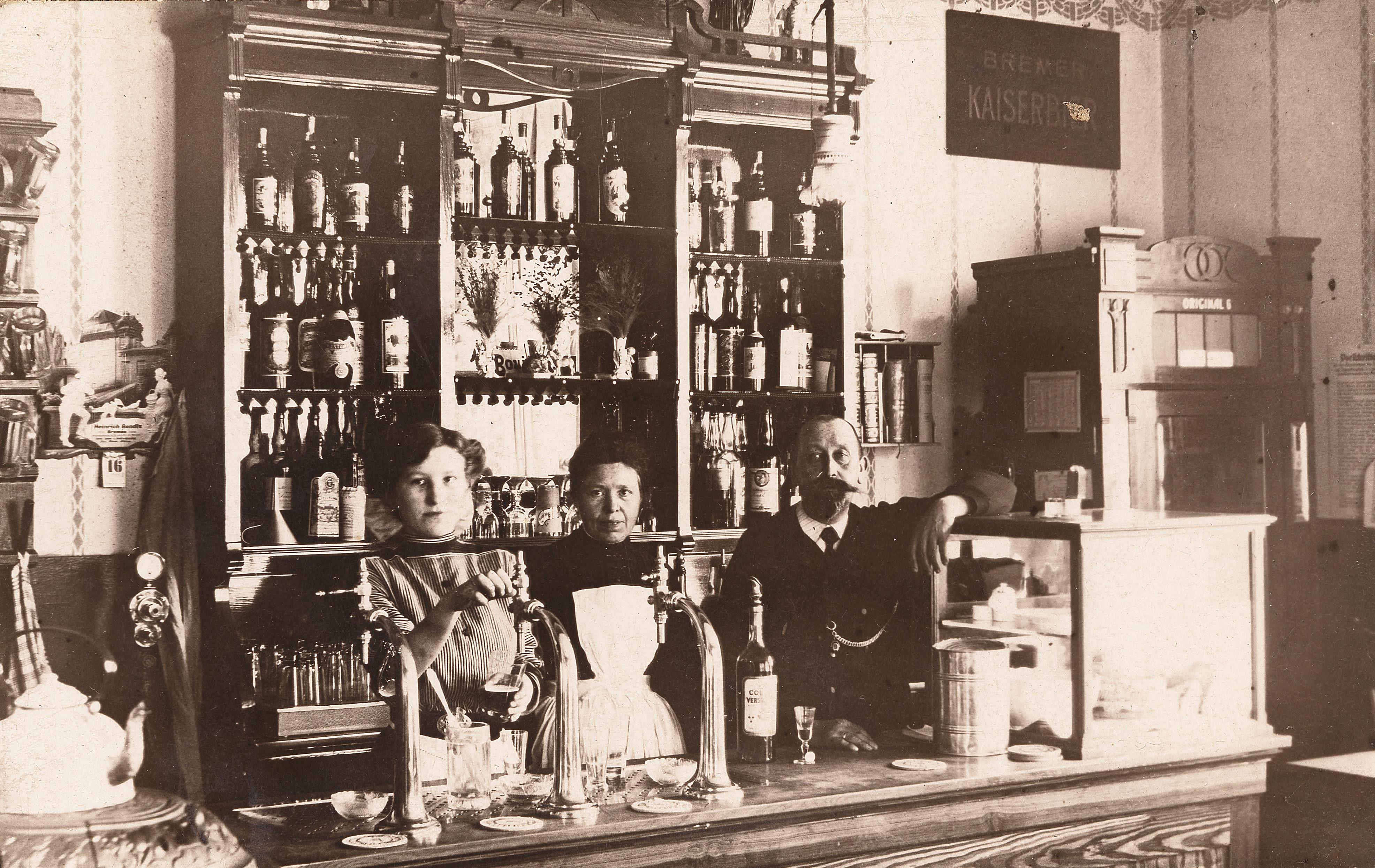 Hoch die Tassen! Am Eröffnungstag, den 16. Oktober 1911, ließen sich die Betreiber ablichten, von rechts: Wilhelm Siemering, den linken Arm auf die Kuchenauslage gelehnt, daneben Ehefrau Sophie in weißer Schürze und die Adoptivtochter Tochter Marie, ein Bier zapfend. Im Hintergrund das Jugendstil-Tresenregal. Quelle: www.gastfeld.de