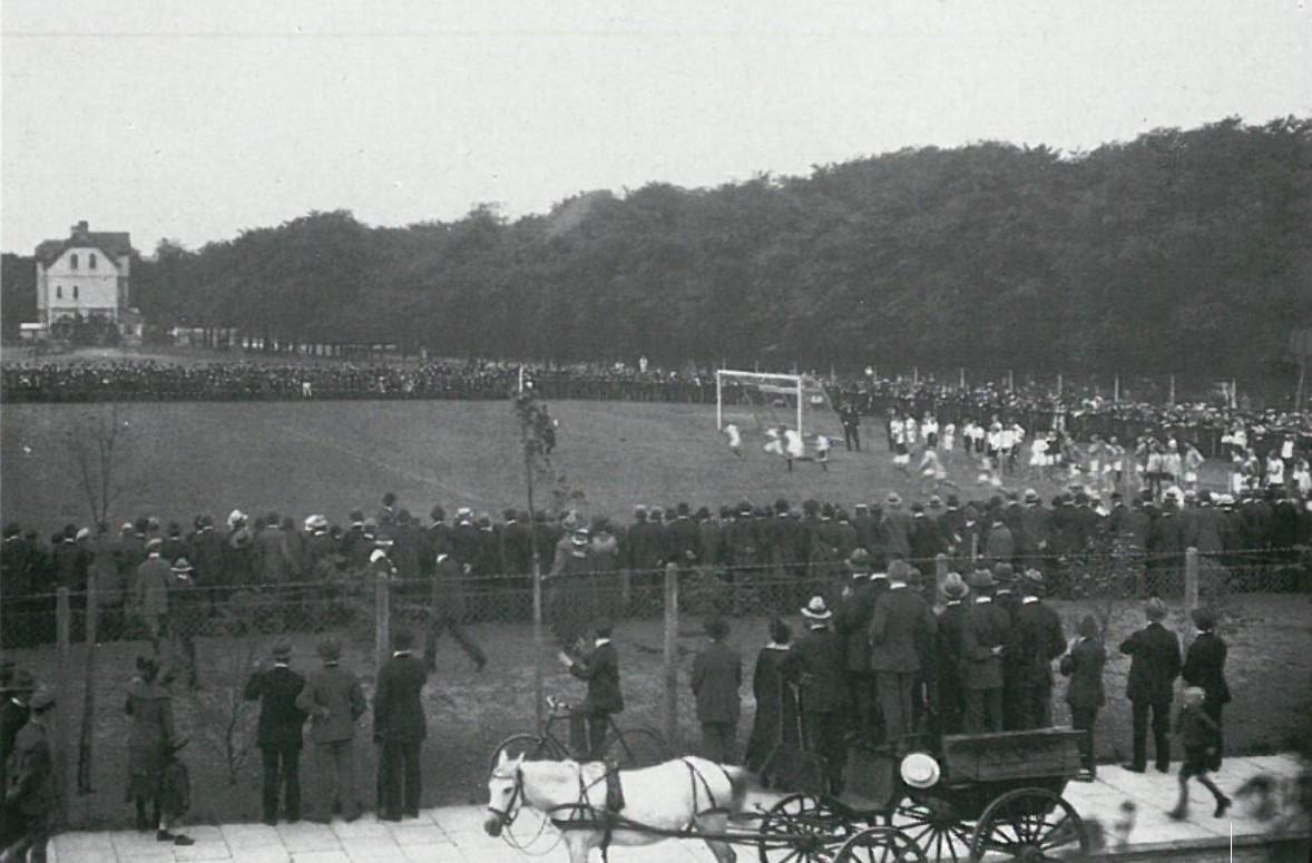 """Am 1. August 1920 wurde der """"Bürgerpark-Sportplatz"""" eingeweiht. Viele Bremer ließen sich dieses Ereignis nicht entgehen. Selbst Zaungäste scheuten sich nicht, dieser Veranstaltung mit dem Pferdewagen beizuwohnen. Auf dem Foto führen die jugendlichen Leichtathleten einen Staffellauf vor. Quelle: Bremer Sport-Verein von 1906 e.V."""