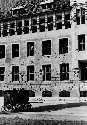 In Mitleidenschaft gezogen: ein abgedecktes Dach und Splitterschäden an der Fassade des Polizeihauses. Quelle: Staatsarchiv Bremen