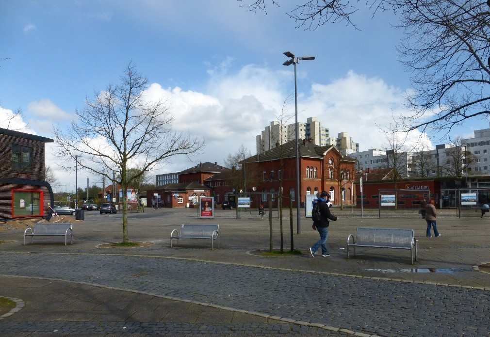 """Der Vegesacker Bahnhof und Bahnhofsvorplatz im April 2016. Im Hintergrund ist der Hochhauskomplex """"Grohner Düne"""" zu sehen. Foto: Peter Strotmann"""