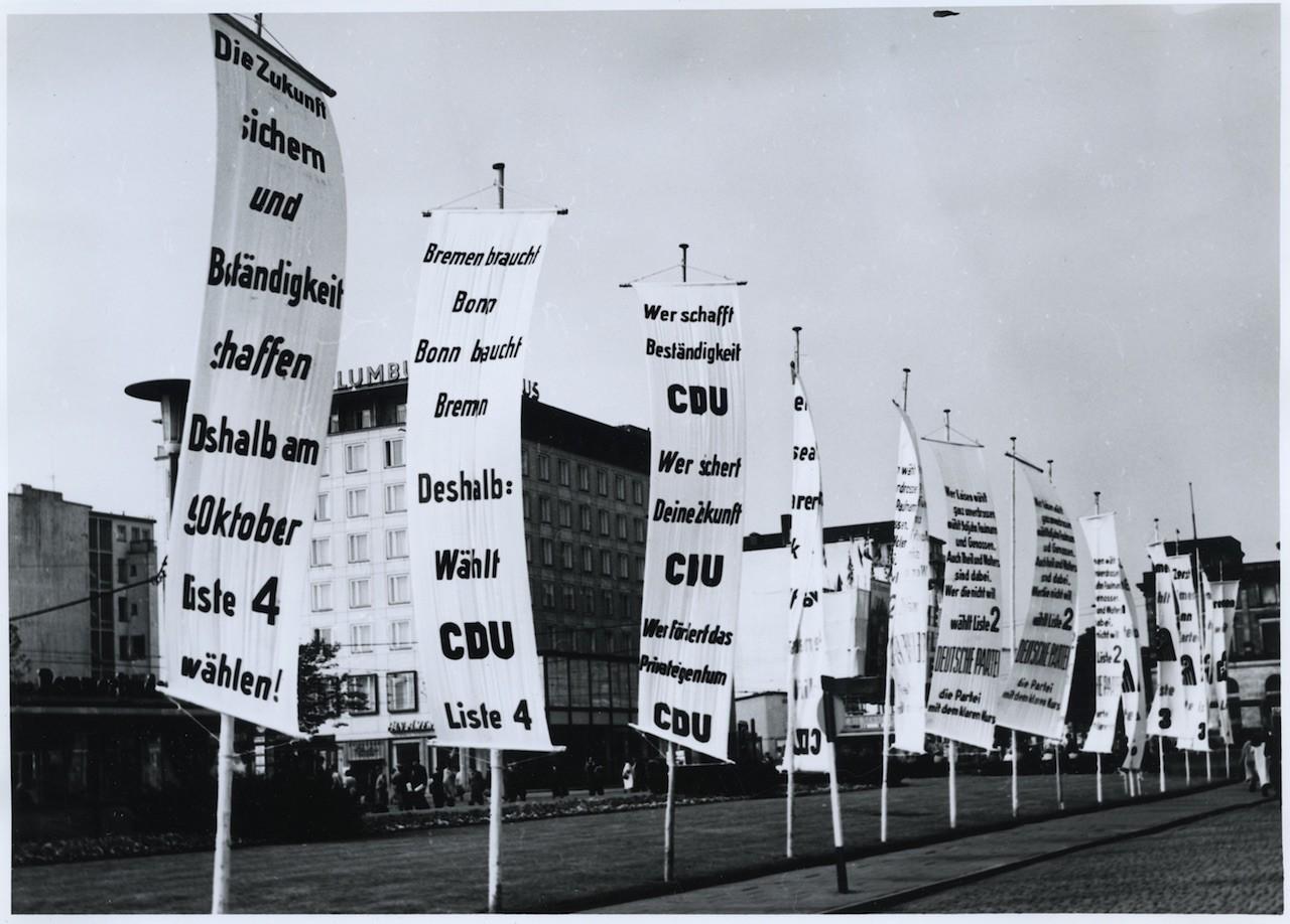 """""""Bonn braucht Bremen, Bremen braucht Bonn"""", Wahlwerbung der CDU auf dem Bahnhofsvorplatz vor der Bürgerschaftswahl 1955, Quelle: Staatsarchiv Bremen, Fotograf: Karl Edmund Schmidt."""