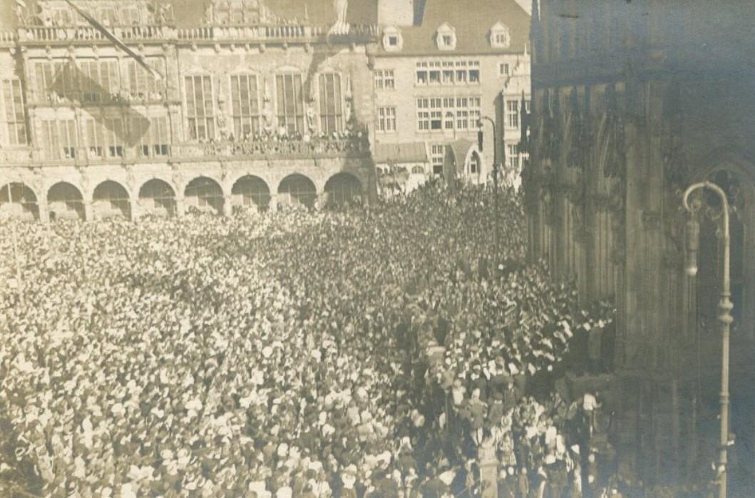 Vor der Neuen Börse: Menschenmassen jubeln der Mannschaft um Kapitän König zu. Rechts vor der Börse steht eine Musikkapelle. Quelle: Staatsarchiv Bremen
