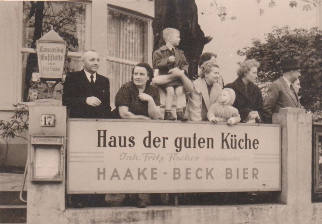 Familienfoto vorm Concordia: Inhaber Fritz Fischer 1956 (r. mit Hut) mit seinem damals zweijährigen Enkel Michael Böhme (auf das Werbeschild gelehnt). Bildvorlage: Michael Böhme