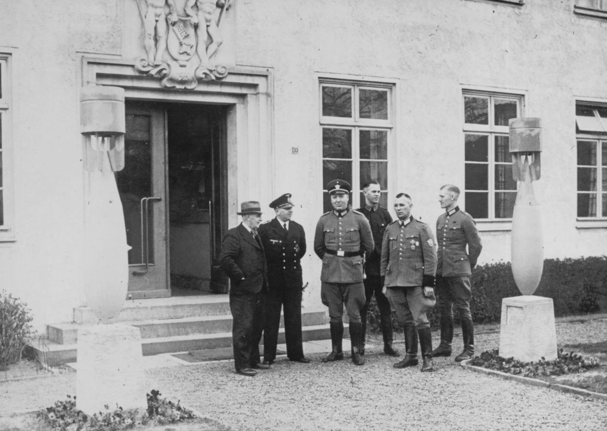 """Die """"Haute-Volaute"""" 1940 vor dem Eingang zum 13. Polizeirevier: Rechts und links sind in den Rabatten je ein Blindgänger als Trophäe aufgestellt. Über dem Türsturz ist ein Relief mit zwei nackten, männlichen Arbeitern angebracht. Quelle: Schwachhausen-Archiv/private Leihgabe"""