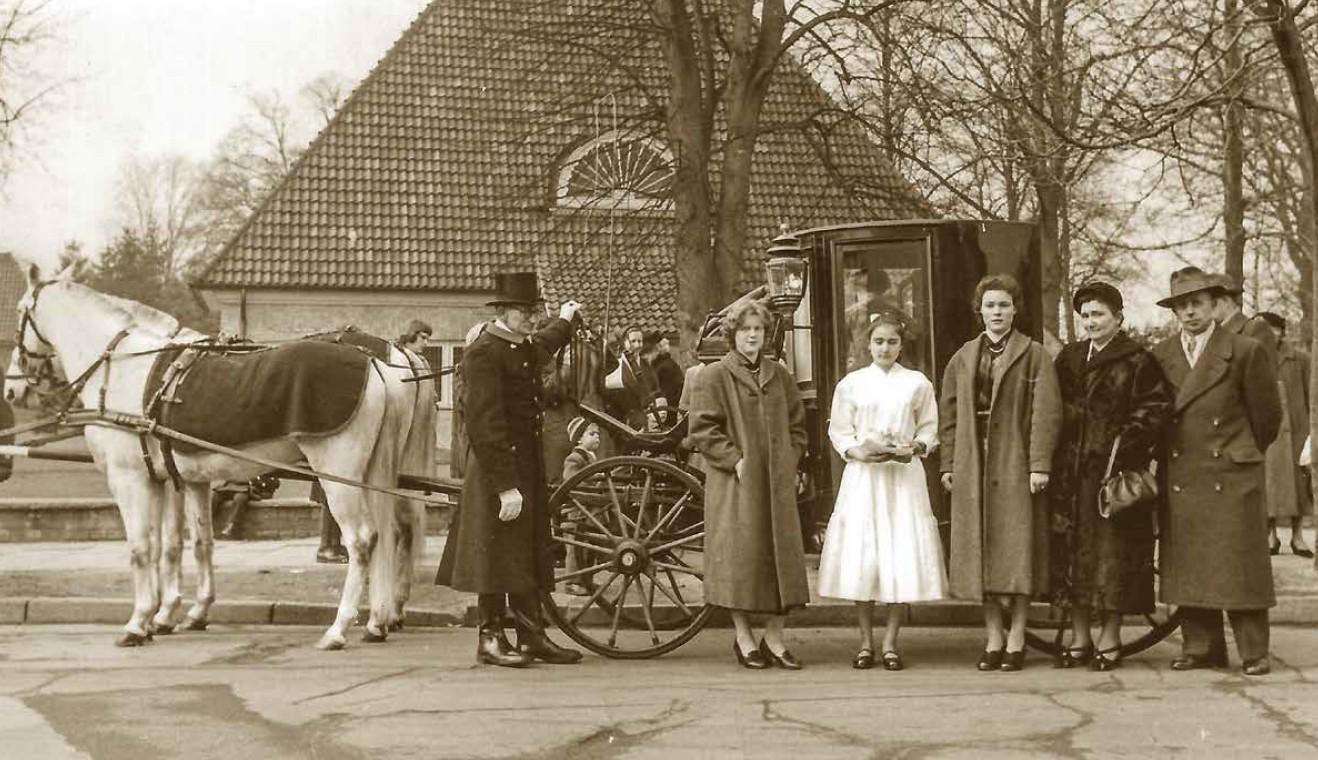 Konfirmandin mit Familie, Kutsche und Bremer Kirche im Hintergrund, aufgenommen 1953 in schwarz-weiß